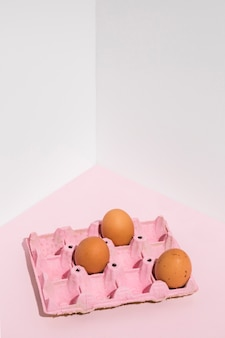 Three brown eggs in pink rack on table