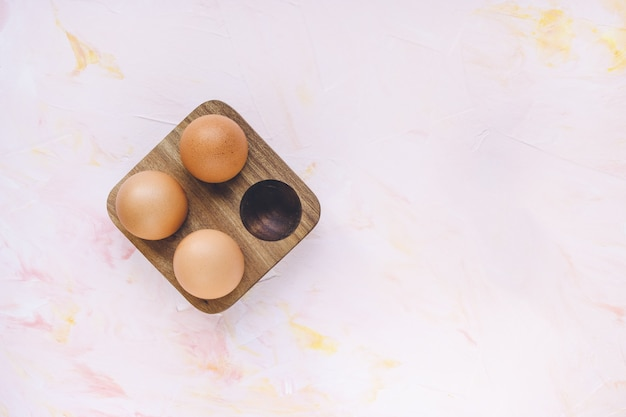 Three brown eggs in a wooden storage organizer box on pink background. useful household items, organic healthy bio product and easter holiday concept. top view, copy space