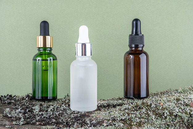 Three brown, green, white glass bottles with serum, essential oil or other cosmetic product on tree bark covered with moss against green background. natural organic spa cosmetic beauty concept.
