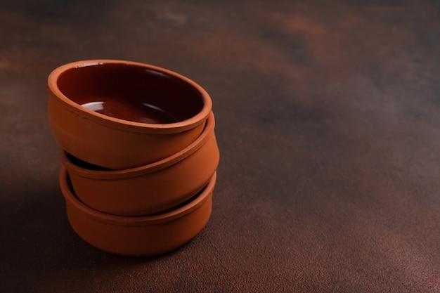 Три коричневые глиняные миски ручной работы на темном столе