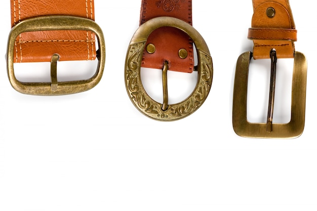 Three brown leather belts with bronze buckles isolated on white background