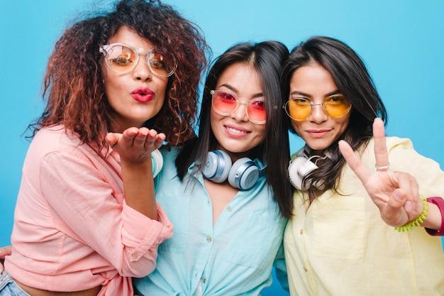 Tre signore castane in occhiali da sole che inviano baci d'aria. ritratto dell'interno della ragazza europea romantica con i capelli lucidi che scherzano con gli amici internazionali.
