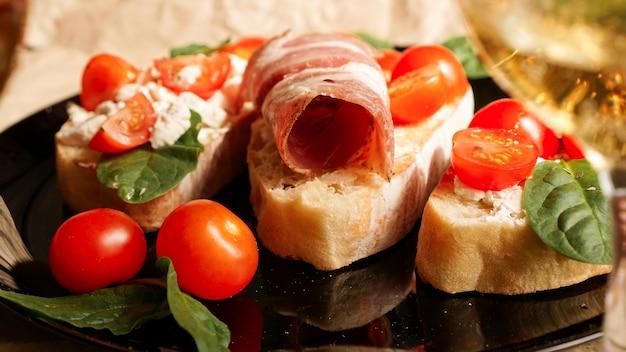 クラフト紙の黒いプレートに3つのブルスケッタ。チェリートマト、豆腐チーズ、ほうれん草、ベーコンの前菜。