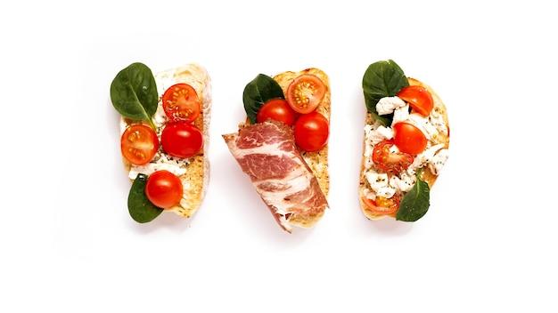 Три брускетты на чиабатте на белой тарелке. итальянская закуска на изолированном фоне. сет с помидорами и беконом