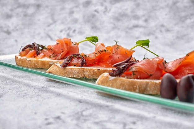 Три брускетты с форелью, лососем, сливочным сыром и микрозеленью на стеклянной тарелке