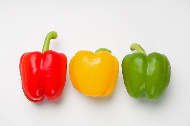 Three bulgarian peppers of different colors lie in a row on a white surface. view from above