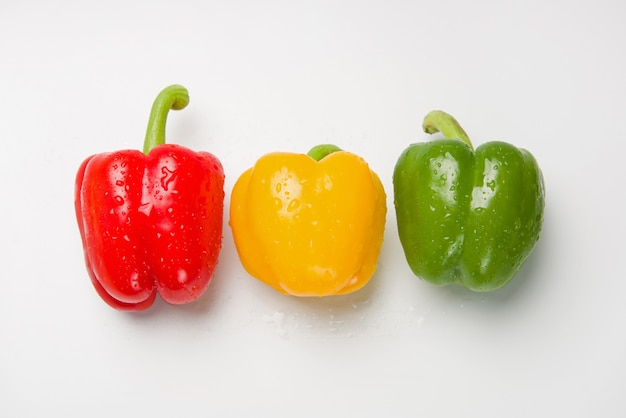 Three bulgarian peppers of different colors lie in a row on a white surface.