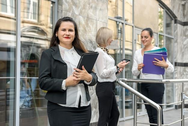 オフィスビルの外で意思決定をする 3 人のビジネスの同僚