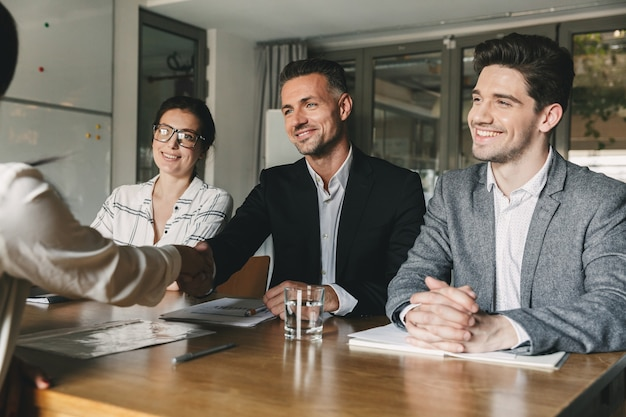 Three business partners in office handshaking with woman, as successful collaboration result or starting partnership after effective negotiations