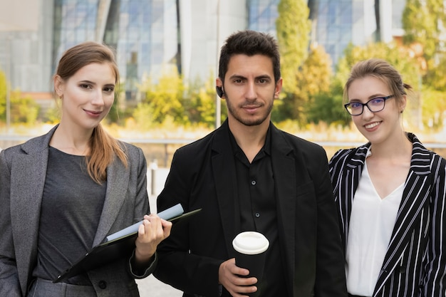 Three business partners stand against the background of an office building. they rejoice and smile, as they managed to successfully negotiate and conclude a deal.