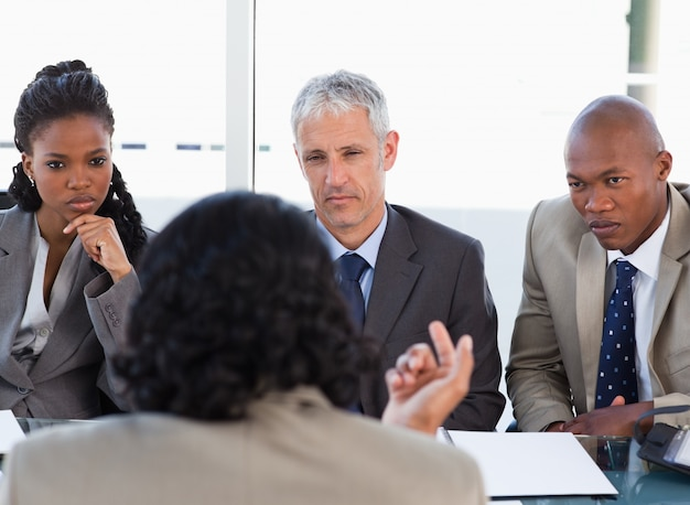 Three business people attentively listening to a speaker in a meeting