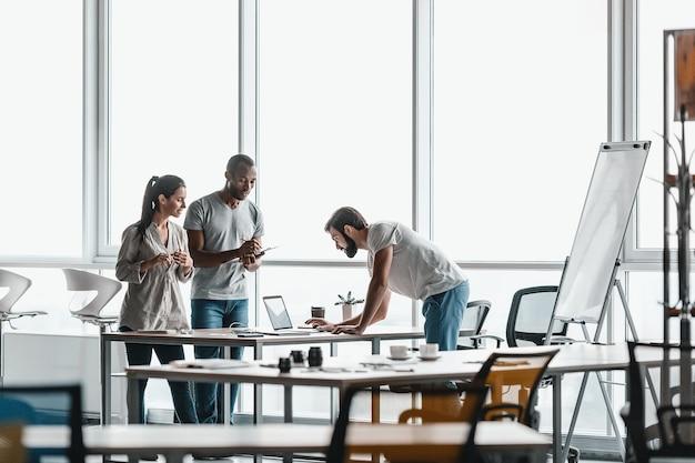 Трое деловых людей в повседневной одежде разговаривают, стоя у деревянного стола в ярком современном офисе. они улыбаются и смотрят друг на друга, обсуждая тему. вид издалека