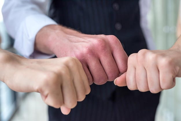 Three business people shaking hands after successful meeting in office hallway.