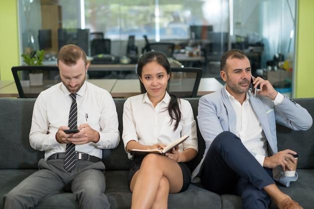 Three business people sitting on sofa and having coffee break