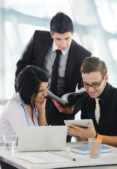 Three business people working at office with folder and documents