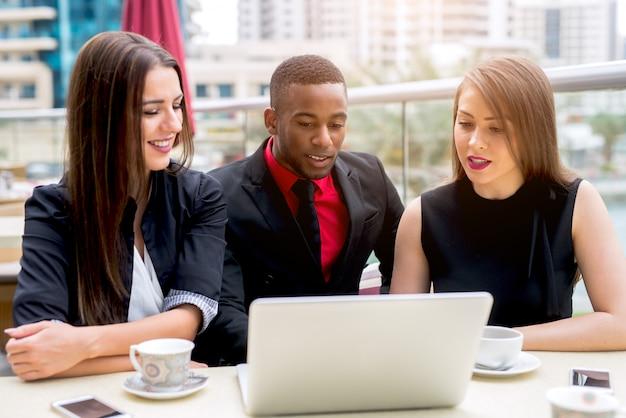 戸外でラップトップに取り組んでいる3つのビジネス人々。