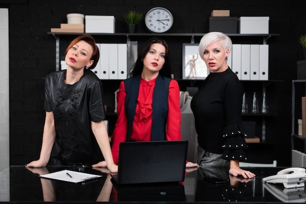 Three business women stand near desk in office