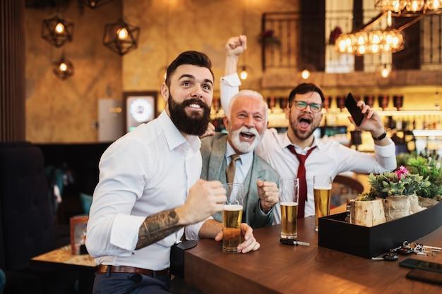 Трое бизнесменов аплодируют во время просмотра футбольного матча в кафе-баре.