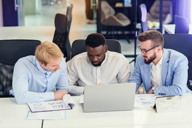 현대적인 사무실 테이블에 앉아 자신의 회사를 성공적으로 개발하기 위해 보고서와 컴퓨터의 데이터를 분석하는 세 사업가. 프리미엄 사진