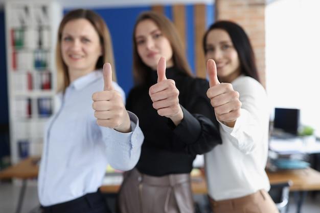 Три бизнесвумен улыбается и держит палец вверх в офисе