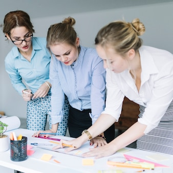 Three businesswomen preparing business chart on desk in office