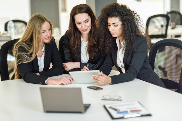 Three businesswomen working together in a modern office