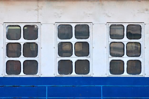 배의 바깥쪽에 있는 3개의 선실 창과 현창. 빈티지 오션 라이너의 선체를 닫습니다. 오래된 배 오두막 창문, 흰색과 파란색 벽.