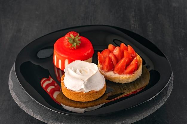 Три торта на черной тарелке. фруктовые десерты со свежей клубникой. кондитерские изделия. нежные десерты