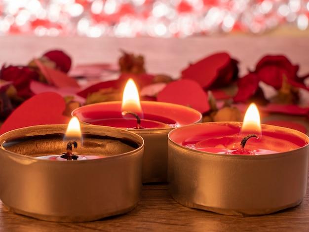 타오르는 세 개의 촛불과 그 뒤에는 테이블에 붉은 장미 꽃잎이 있습니다.