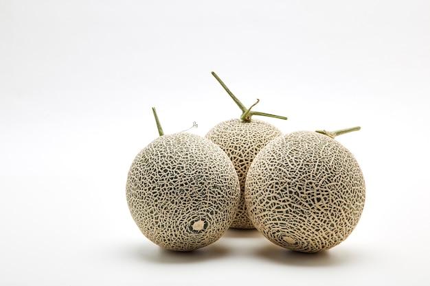Three cantaloupe melon on white