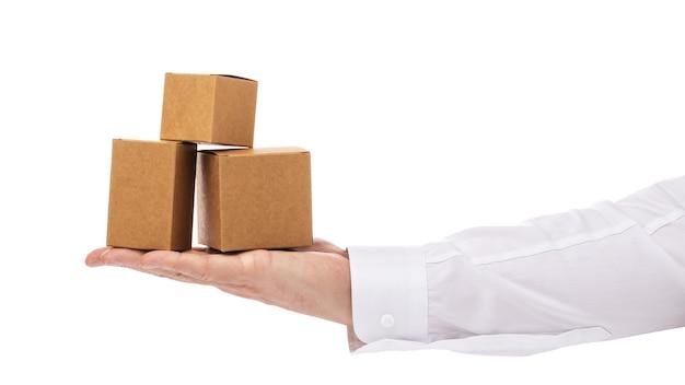 Три картонные коробки разных размеров на ладони мужчины, изолированные на белом фоне