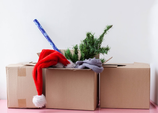 Three cardboard boxes one contains an artificial christmas tree santa hat and wrapping paper.
