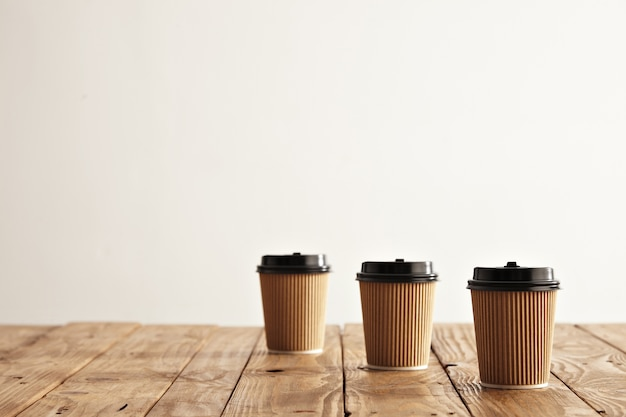 Three carton paper cups in row isolated on right side of rustic wooden table