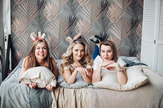 잠옷을 입은 백인 여자 친구 3명이 함께 즐거운 시간을 보낸다