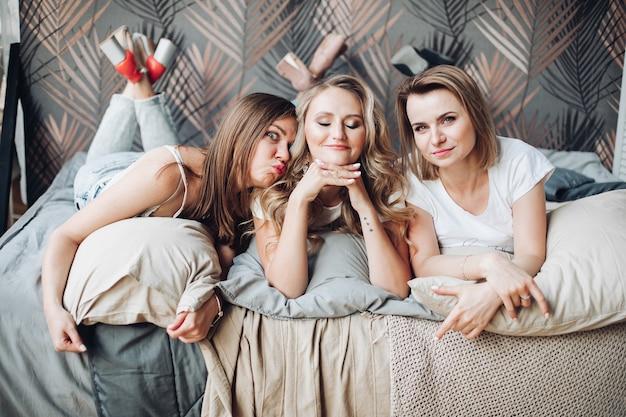 Tre amiche caucasiche in pigiama si divertono molto insieme
