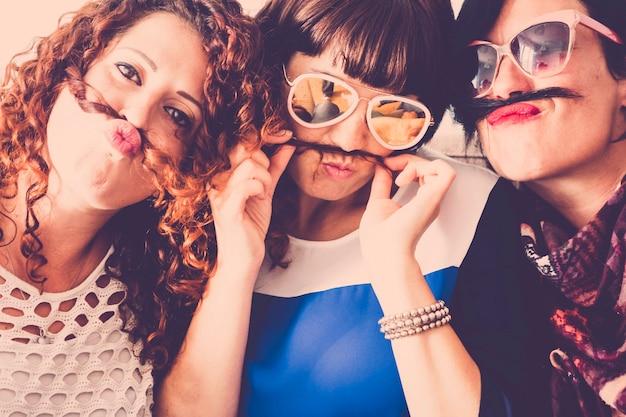3 人の白人の女性の友人は、口ひげのような髪と幸福の関係の概念を使用して、友情と狂気の中で一緒にいます
