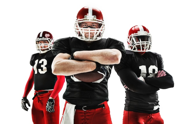 The three caucasian fitness men as american football players posing with a ball on white background