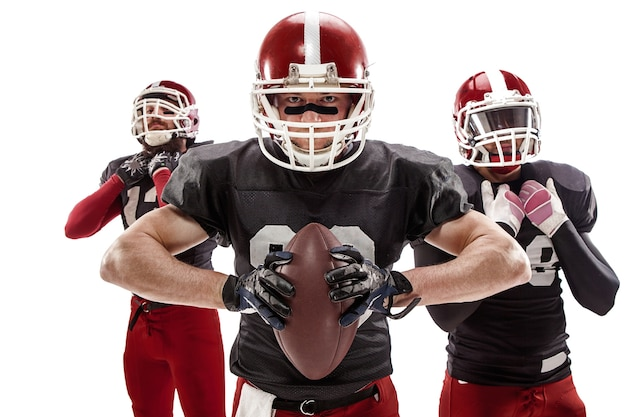 The three caucasian fitness men as american football players posing with a ball on white