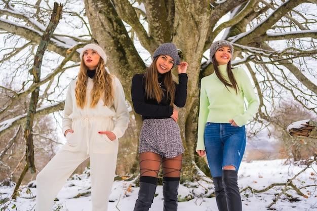 木の下で冬の雪を楽しんでいる3人の白人の友人 Premium写真