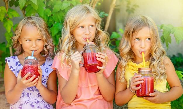야외에서 수박 스무디를 마시는 세 백인 여자. 여름 레저 개념입니다.
