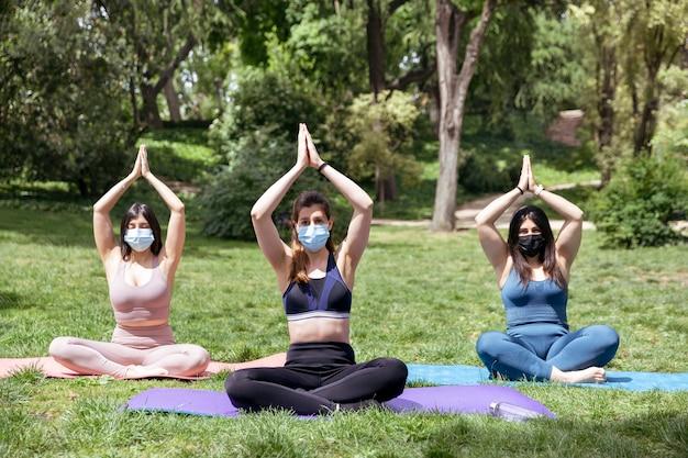 屋外でヨガを練習しているフェイスマスクを持つ3人の白人の女の子。テキスト用のスペース。