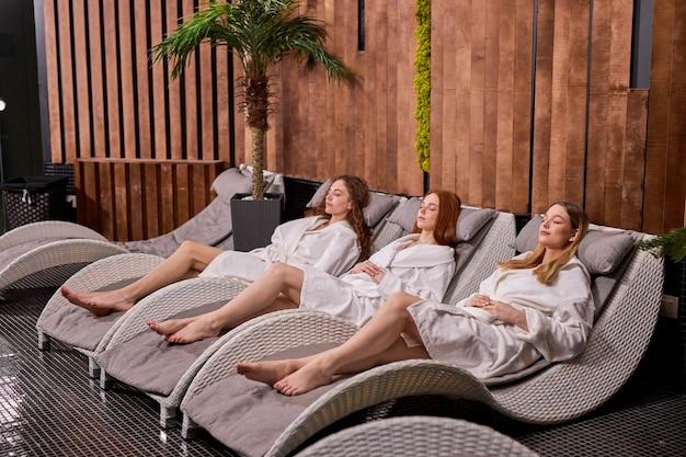 목욕 가운, boodycare 및 건강한 라이프 스타일 컨셉을 입고 스파 후 휴식을 취하는 세 백인 편안한 여성