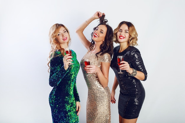 一緒に時間を楽しみ、ワインを飲み、踊るキラキラと輝く夜の服装で祝う3人の女性