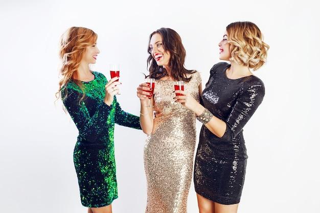 Tre donne in festa in abito da sera scintillante che si godono del tempo insieme, bevono vino e ballano. sfondo bianco.