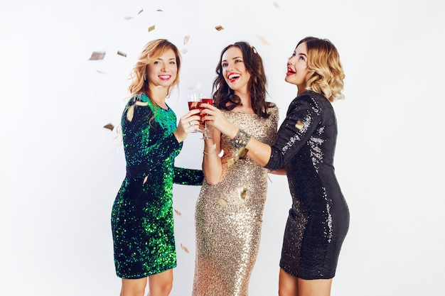 Three celebrating women in sparkly  evening outfit  enjoying  time together , drinking wine and dancing