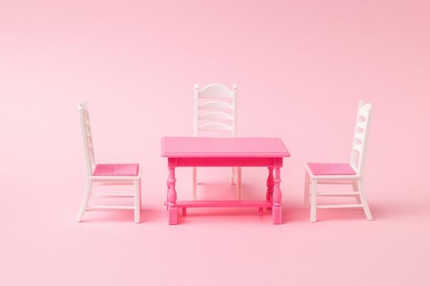 ピンクの表面の赤いテーブルの近くにある3つの椅子
