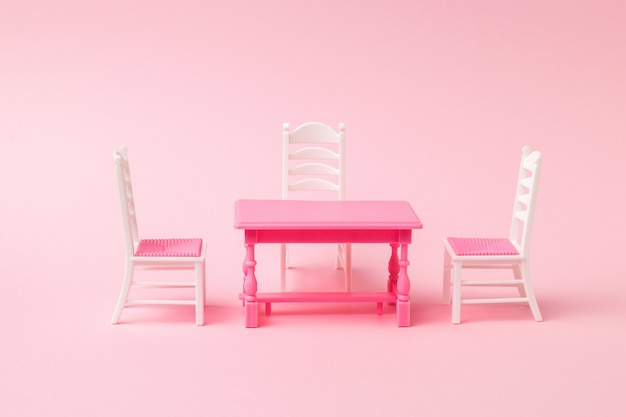 Three chairs near a red table on a pink surface