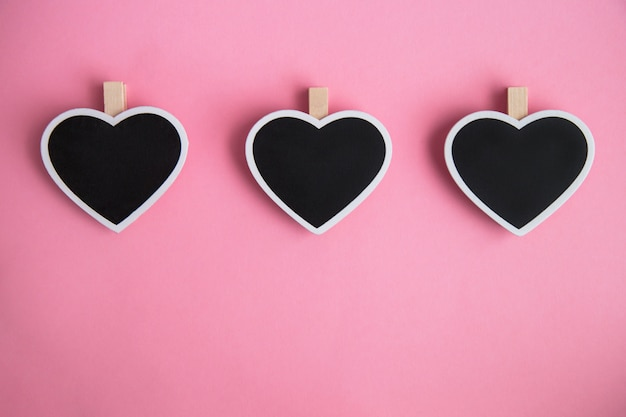 Three chalk board for notes in shape of heart on pink background