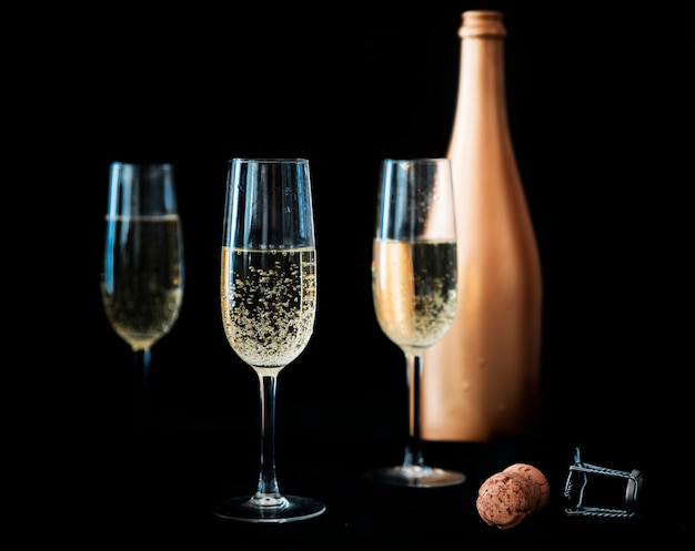 Three champagne glasses with bottle