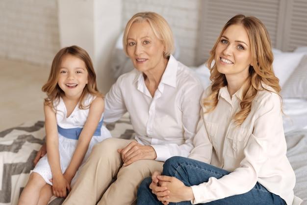 서로 다른 나이의 매력적인 세 여성이 함께 즐거운 시간을 보내고 침대에서 서로 유대를 맺고 함께 있으면 행복해 보입니다.